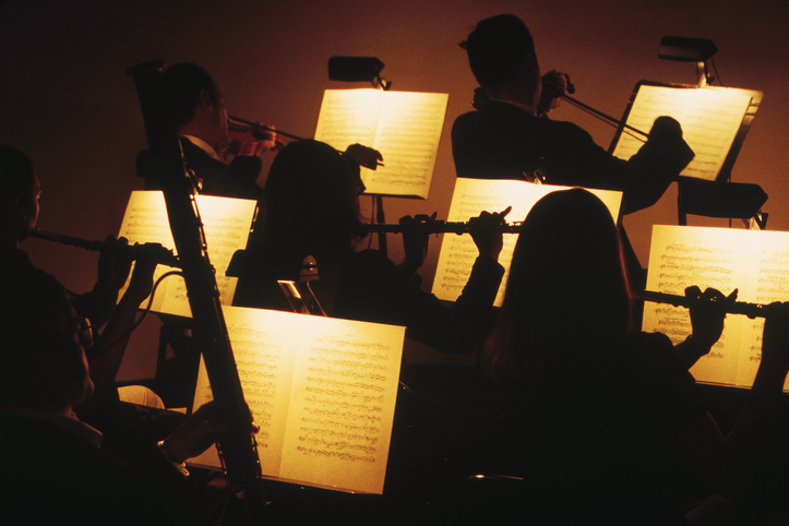 View of symphony orchestra performing from sheet music